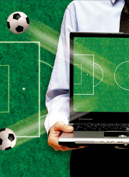 Persona sosteniendo un portátil en el que se puede ver un encuentro de fútbol